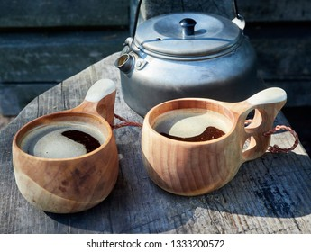 Two wooden mugs filled with hot fresh coffee on the campsite while trekking. Selective focus, slightly blurred background. Consept of adventure and freedom