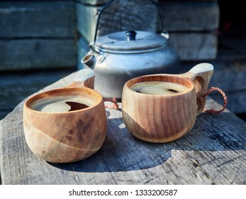 Two wooden mugs filled with hot fresh coffee on the campsite while trekking. Selective focus, slightly blurred background. Consept of adventure and freedom.