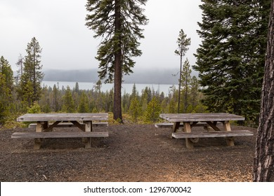 Two wooden picknic tables at a viewing area with Diamond Lake in the distance on a foggy afternoon in Oregon.