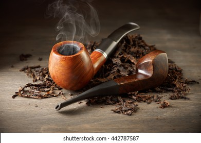 Two wooden pipe with smoke and tobacco pile on vintage wood.