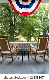 Two Wooden Rocking Chairs with Small Table at the Terrace with Conceptual American Flag Fronting Tall Green Trees at the Garden