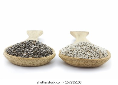 two wooden spoons with black and white chia seeds isolated on white