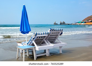 Two wooden sun loungers with white umbrella standing on the beach of Arambol in the water.North Goa.India