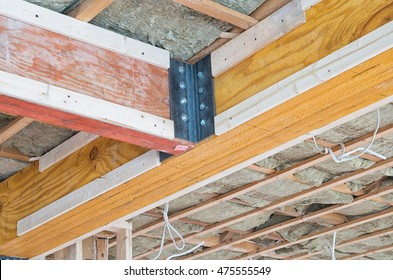 Two wooden supporting beams intersecting on ceiling of house