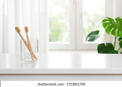 Zwei hölzerne Zahnbürsten in Glas auf verschwommenem Hintergrund