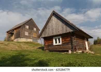 Two wooden village houses on a sunny onion. Carpathians, Ukraine
