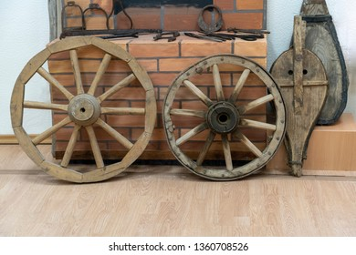 two wooden wheels from the cart on the background of a brick blacksmith shop, fur to inflate the fire in the fireplace