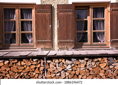Two wooden windows and a stack of wood on a wall of a farmhouse.