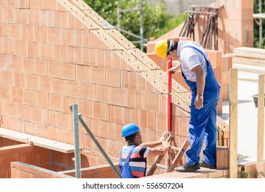 Two worker controlling construction or building site walls