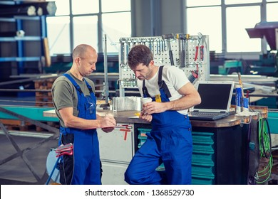 two worker in factory on work bench in conversation