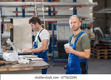 two worker in factory on work bench