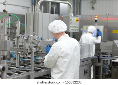 two workers in aprons and caps  at production line in plant
