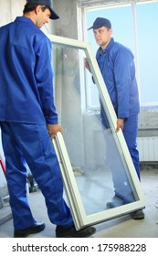 Two workers in blue work clothes carry the window to install it in the frame