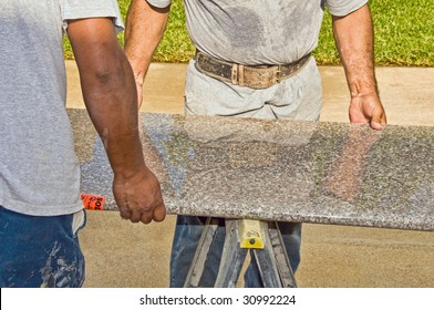 Two workers carry a large slab of granite into place