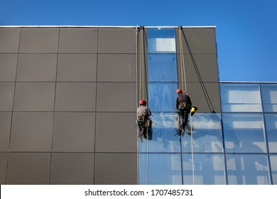 Two workers cleaning glass facade, hanging on rope like alpinist