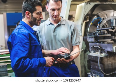 Two workers discussing a project in front of CNC lathe machine writing in clipboard