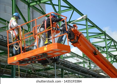 Two workers are driving the Orange articulate boom lift or telescopic boom lifts and bucket crane mounted on truck to safety for working at heights and articulating boom lift reaching high up.