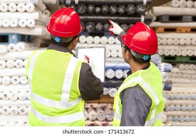 Zwei Arbeiter stellen Textilbearbeitung und Kontrolle von Rohstoffen in Lagerhäusern