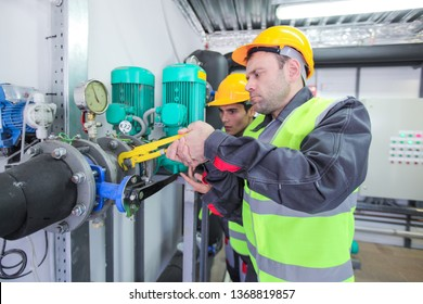 Two workers fixing pipes with manometer on high pressure system at factory