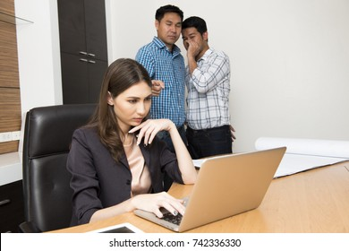 Two workers gossip the lady boss while she playing and chatting on social network with computer .