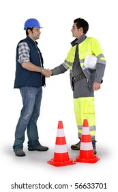 Two workers handshaking on white background