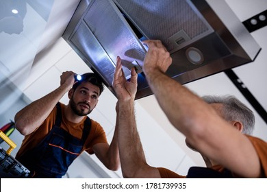 Two workers, handyman in uniform installing or repairing a kitchen extractor, replacing filter in cooker hood. Construction, maintenance and repair concept. Low angle. Focus on hand and filter