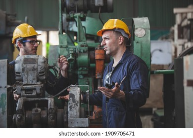 Two workers at an industrial. technician engineer checking process on notebook to machinery in factory. workers using machine equipment in factory