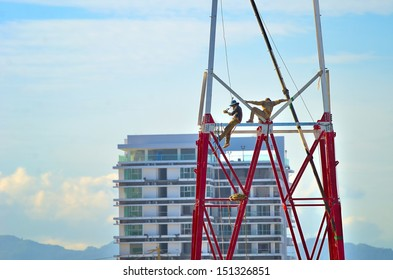 Two workers install a lot of Metal tiered tower