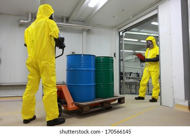 Two workers in protective uniforms,masks,gloves and boots, working with barrels of chemicals on forklift in factory