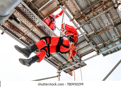Two workers with red boiler suit work at height one of them low down by rope access