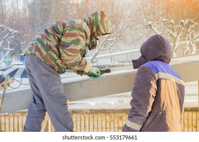 Two workers repairing the roof of the underpass winter outdoors