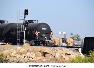 Two workers safeguard the transportation of petroleum tanks, Kern county, Bakersfield, CA, October 1, 2018.