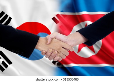 Two workers shaking hands after negotiation in front of the north and south korean flags