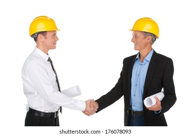 two workers shaking hands and smiling. engineers wearing yellow hardhat and standing