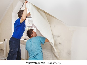 two workers smoothing wallpaper in their house