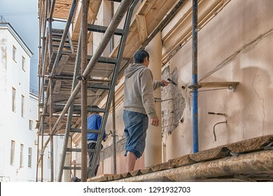 Two workers standing on scaffolding, perform work on the restoration of the facade of the old building.