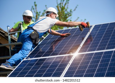 Two workers technicians installing heavy solar photo voltaic panels to high steel platform. Exterior solar system installation, alternative renewable green energy generation concept.