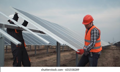 Two workers in a uniform and hardhat install photovoltaic panels on a metal basis on a solar farm