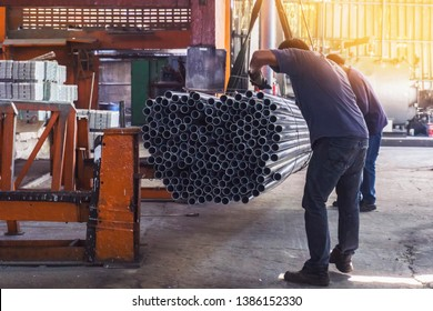 Two workers in uniform using lifting machines to move metal pipe in a sheet metal factory.