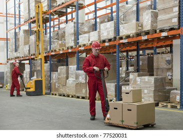 Two workers in uniforms and safety helmets working in storehouse