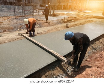 Two workers are using steel box on concrete slabs after pouring concrete,select focus and Light fair.Workers are leveling poured liquid concrete on a steel reinforcement to form strong floor slab.