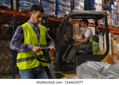 Two workers of warehouse concentrated on their work with goods. Handsome loader in reflective waistcoat operating stacker. Forklift operator in uniform managing forklift.