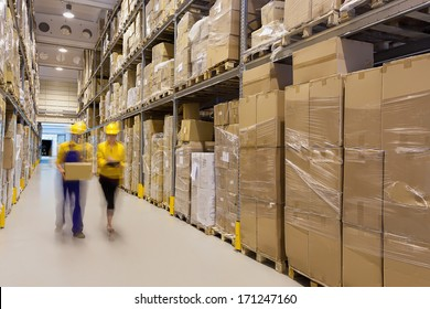 Two workers in warehouse controlling products