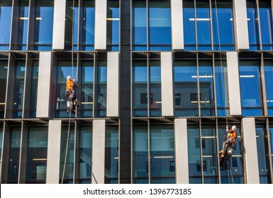 Two workers wash the glass in a modern office building, using the technique of climbing