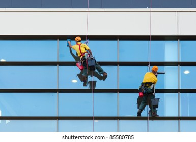 Two workers washing windows of the modern building.