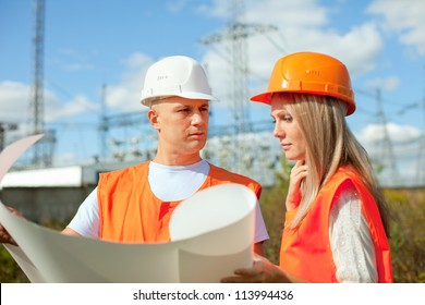 two workers wearing protective helmet works at electrical power station. Focus on man