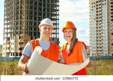 two workers wearing protective helmet works on the building site