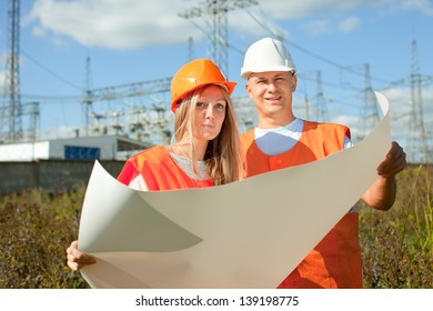 two workers wearing protective helmet works at electric power plant