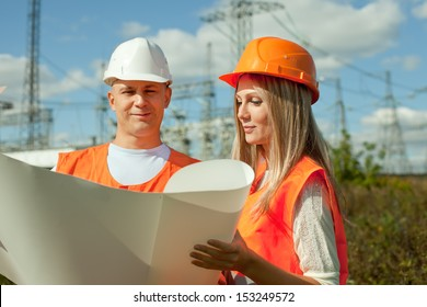 two workers wearing protective helmet works at electrical power station