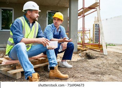 Two workers wearing protective helmets taking break from work and enjoying lunch while sitting outdoors, unfinished building on background